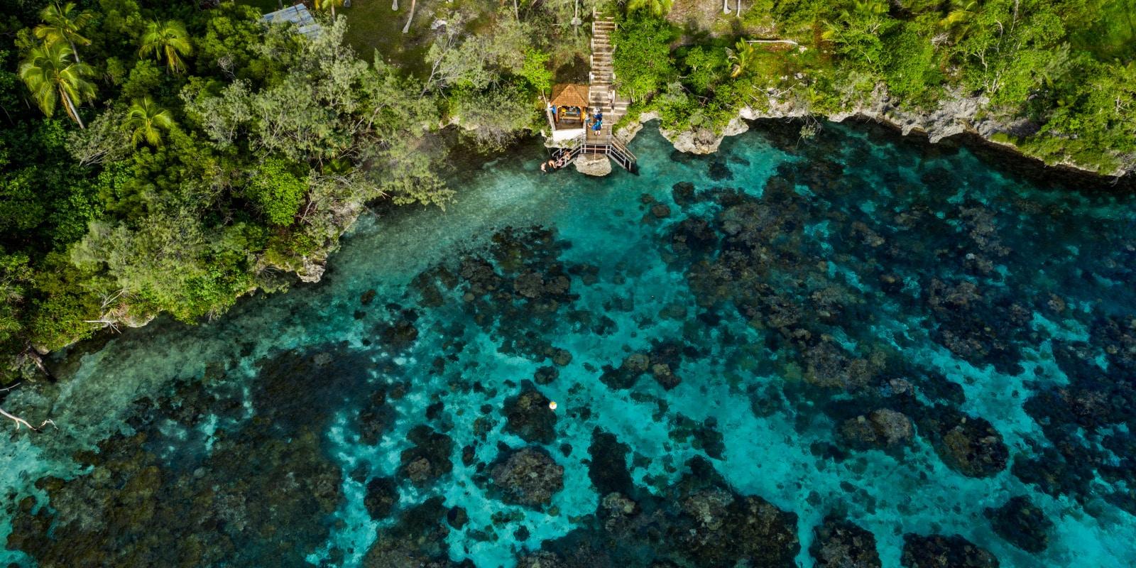 Vue aérienne sur une baie rocheuse donnant sur un lagon corallien en Nouvelle-Calédonie