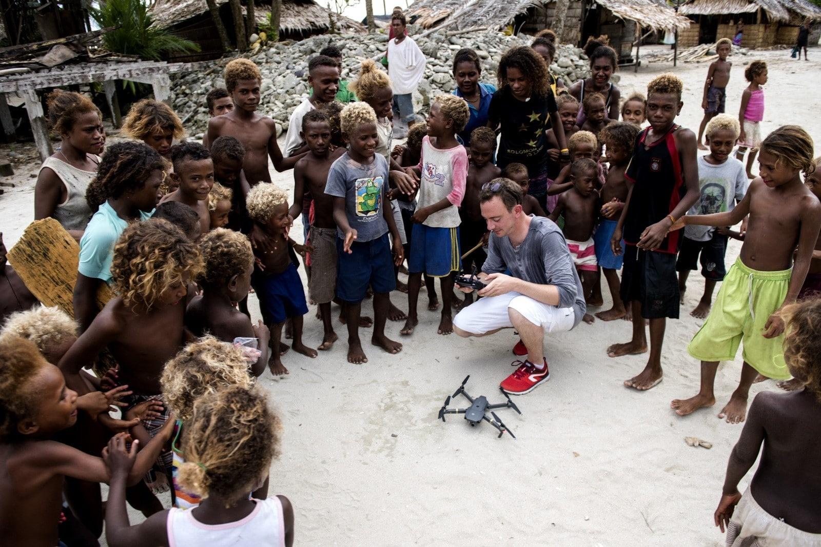 Groupe d'enfants entourant un videaste accroupi devant un drone